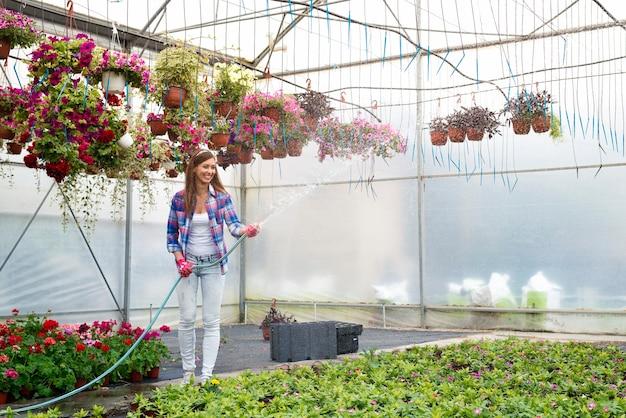 Weibliche floristenarbeiterin, die pflanzen im gewächshaus sprüht und gießt