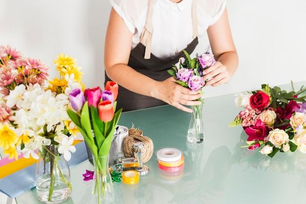 Weibliche floristenhand, die blumen in vase auf glasschreibtisch setzt
