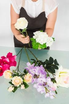 Weibliche floristenhand, die weiße blumen hält