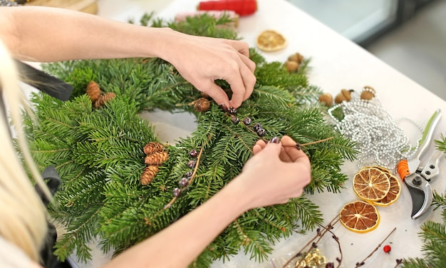 Weibliche floristin macht weihnachtskranz im blumenladen