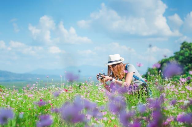 Weibliche fotografie mit der kamera, die ein foto der blume macht