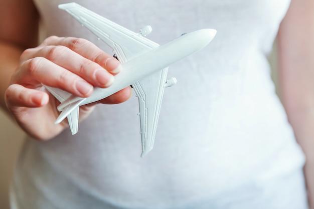 Weibliche frauenhände, die kleines spielzeugmodellflugzeug halten