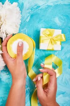 Weibliche frauenhand, die weißes geschenk mit gelbem band einwickelt