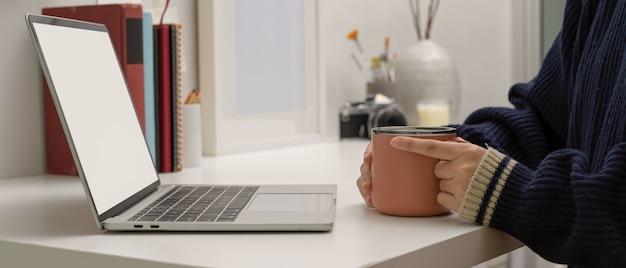 Weibliche freiberuflerin, die zu hause büro sitzt und kaffeetasse hält, während auf schein-laptop schaut
