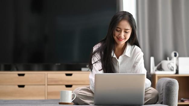 Weibliche freiberuflerin in ihrer freizeitkleidung, die am laptop arbeitet und auf dem sofa im wohnzimmer sitzt.