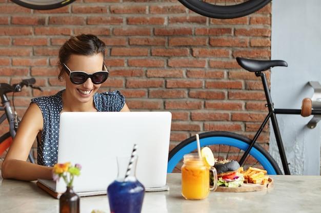 Weibliche freiberuflerin mit glücklichem lächeln, die entfernt auf laptop arbeitet. erfolgreiche food-bloggerin, die einen neuen beitrag in ihrem blog schreibt