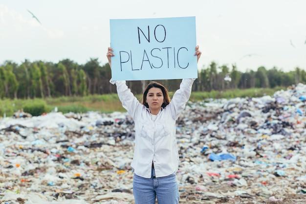 Weibliche freiwillige demonstriert eine mülldeponie mit einem plakat ohne plastik, aktivistin kämpft mit umweltverschmutzung