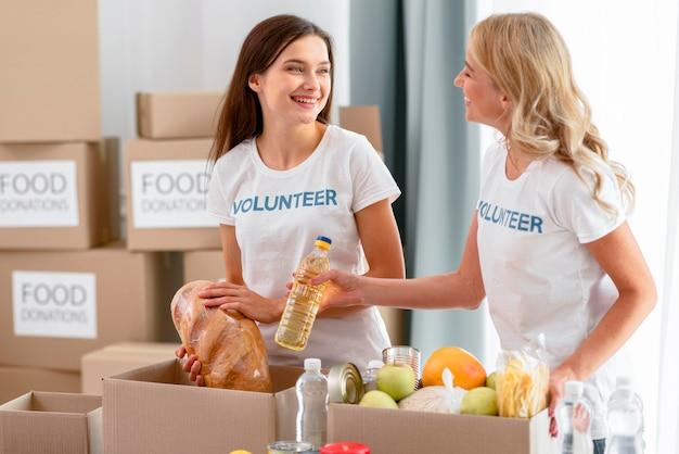 Weibliche freiwillige, die lebensmittel für spenden vorbereiten