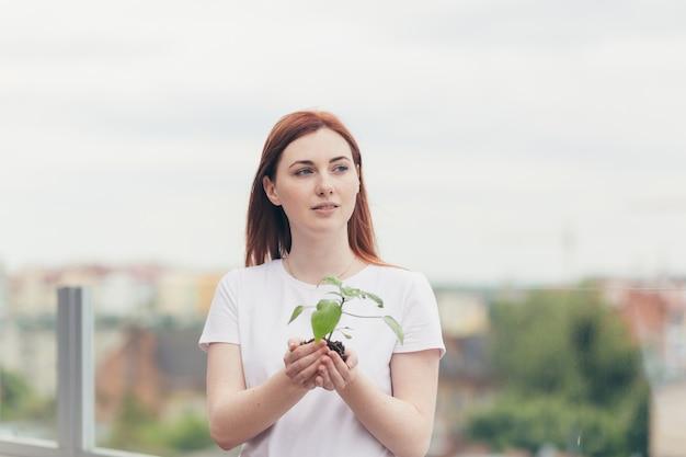 Weibliche freiwillige hält in ihren händen einen sämling eines blumenbaums