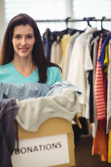 Weibliche freiwillige halten kleidung in spendenbox