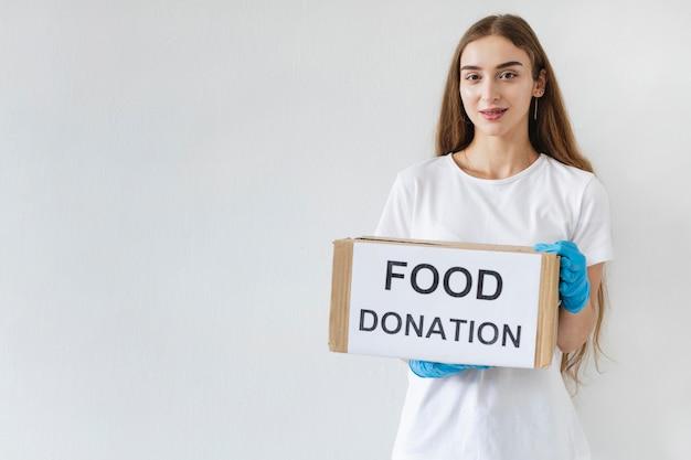 Weibliche freiwillige mit handschuhen, die spendenbox mit kopienraum halten