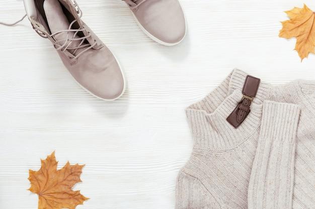 Weibliche freizeitkleidung für herbstwetter, leichte lederstiefel und warme strickpullover. flache lage mit bequemer kleidung auf weißem holzschreibtisch. einkaufsübersicht konzept.