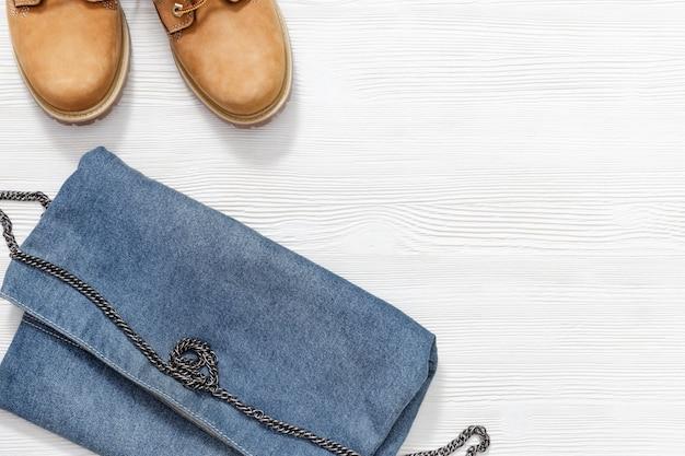 Weibliche freizeitkleidung, orangefarbene lederstiefel und kleine jeanstasche oder clutch. flache lage mit kopienraum auf weißem hölzernem schreibtisch. einkaufsübersicht konzept.