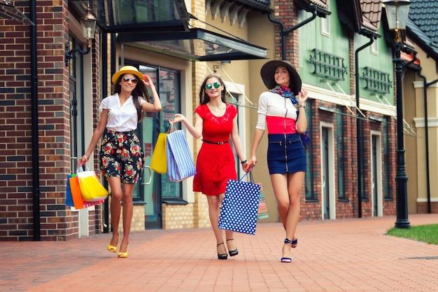 Weibliche freundinnen der recht glücklichen hellen frauen in den bunten kleidern, in den hüten und in den hohen absätzen mit einkaufstaschen gehend an der straße nach dem einkauf