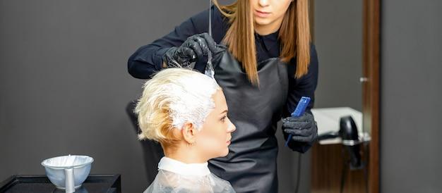 Weibliche friseure, die haare der jungen kaukasischen frau im friseursalon färben