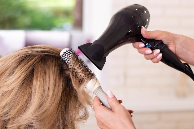 Weibliche friseure handbürsten und föhnen blonder haare im schönheitssalon