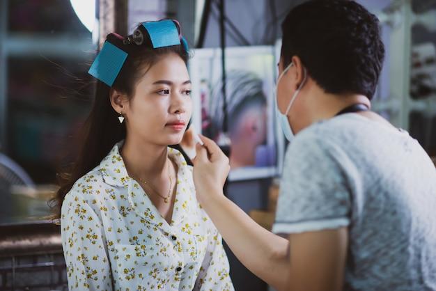 Weibliche friseurstellung, gesichtsmake-up und frisur zur netten reizenden jungen frau im schönheitssalon machen