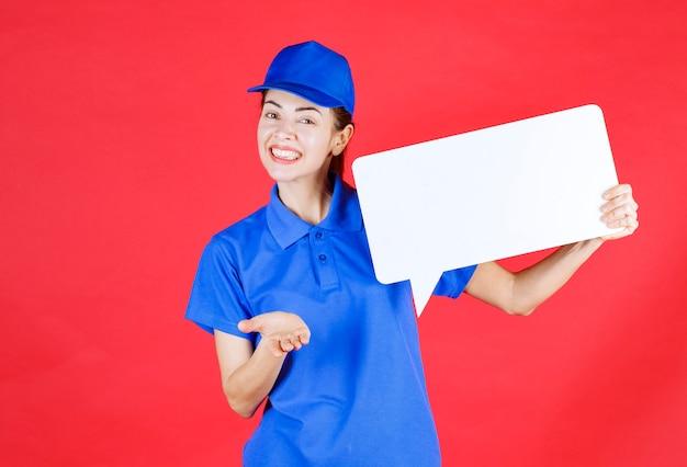 Weibliche führerin in blauer uniform, die eine weiße rechteckige infotafel hält und die person, die vorangeht, zur teilnahme einlädt.