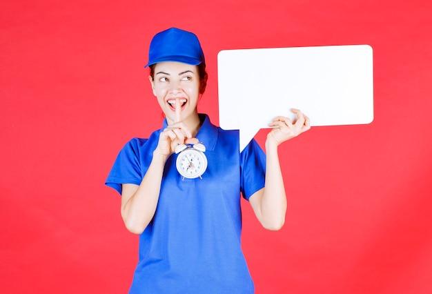 Weibliche führerin in blauer uniform, die eine weiße rechteckige infotafel mit wecker hält und um stille bittet.