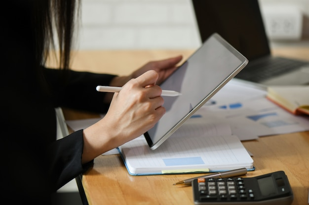 Weibliche führungskräfte verwenden einen aufnahmestift auf dem tablet.