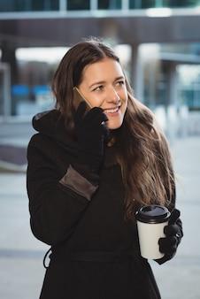 Weibliche führungskraft, die auf mobiltelefon spricht, während kaffee trinkt