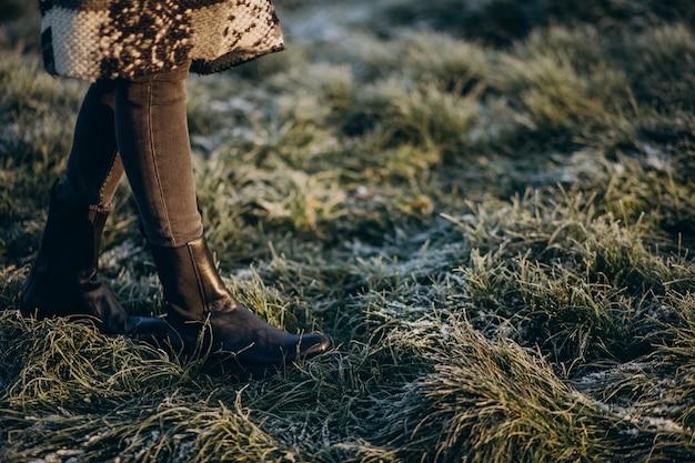Weibliche füße auf dem mit raureif bedeckten gras