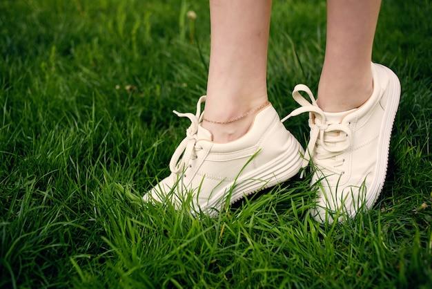 Weibliche füße auf dem rasenspaziergang im park im freien
