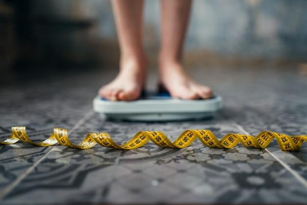 Weibliche füße auf der waage, maßband. konzept zur fett- oder kalorienverbrennung. gewichtsverlust, harte diät