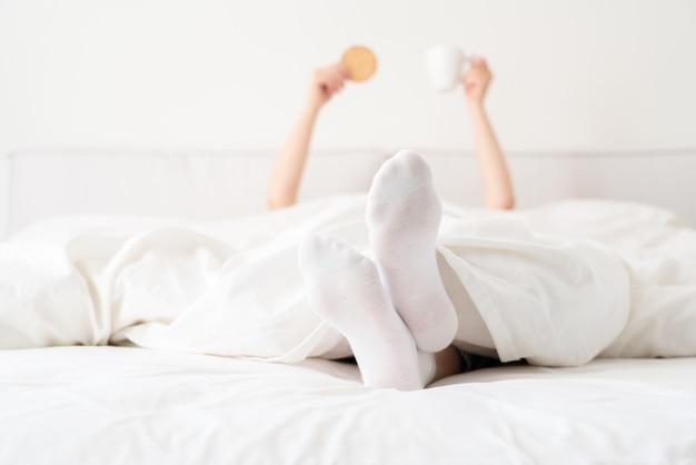 Weibliche füße, die weiße socken unter decke im bett tragen. frau, die morgens aufwacht