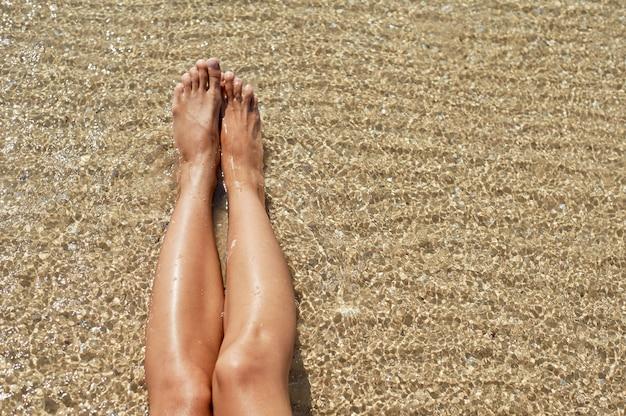 Weibliche füße gegen das meer am sommerstrand.