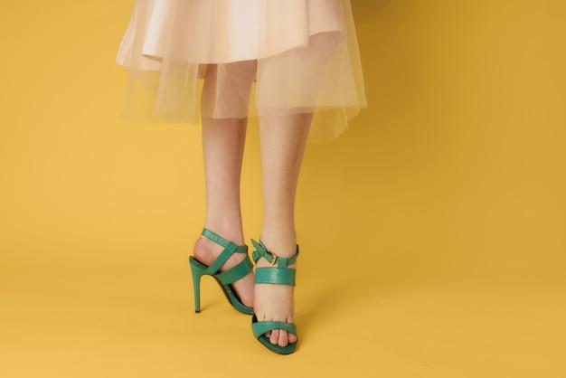 Weibliche füße grüne schuhe elegante art modische schuhe gelbe wand.