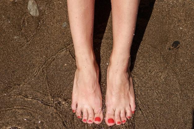 Weibliche füße im sand auf see