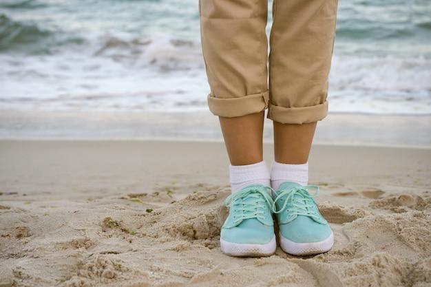 Weibliche füße in den beige hosen und in turnschuhen eines türkises, die auf dem strand stehen