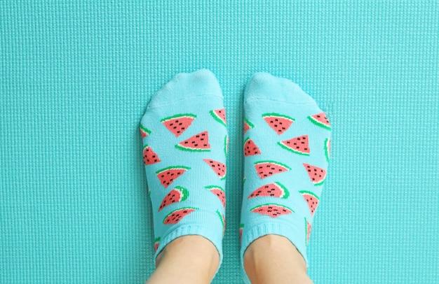 Weibliche füße in den bunten socken im wassermelonendruck auf einem tadellosen pastellhintergrund.