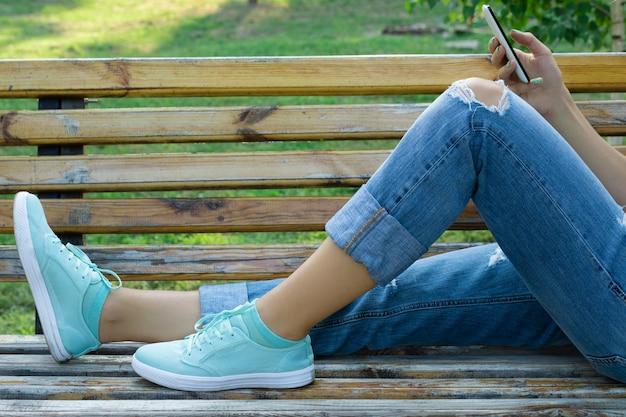 Weibliche füße in der blue jeans und in einer nahaufnahme des handys in der hand