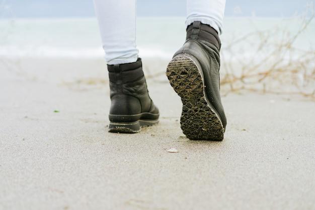Weibliche füße in der blue jeans und in schwarzen winterstiefeln, die auf dem strand gegen das meer stehen
