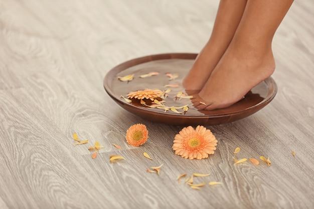 Weibliche füße in der spa-schüssel auf holz