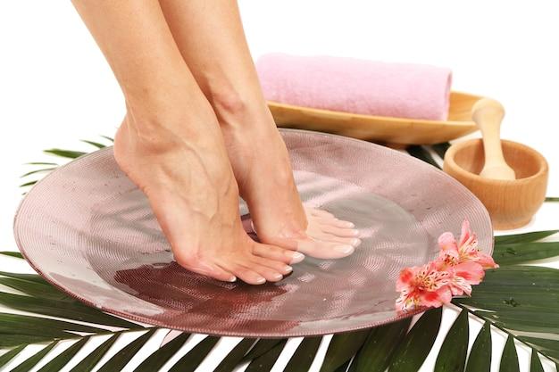 Weibliche füße in der spa-schüssel mit wasser, lokalisiert auf weiß