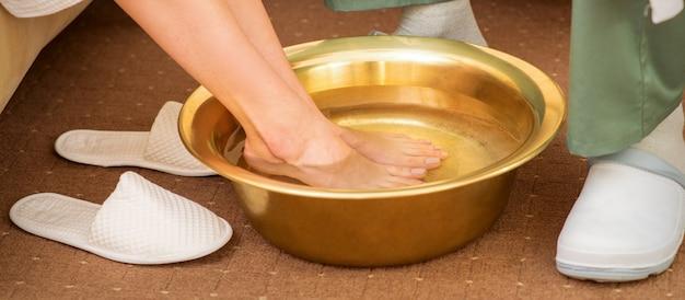 Weibliche füße in einer goldenen schüssel mit wasser im spa-salon. spa-behandlung.