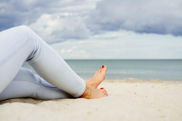 Weibliche füße in jeans am strand sand