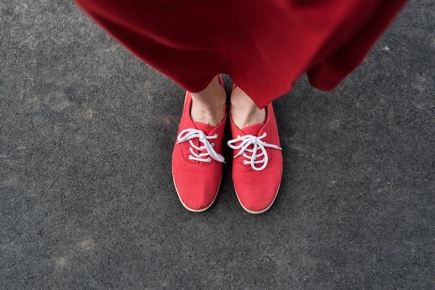 Weibliche füße in roten turnschuhen auf der pflasterung. sicht von oben
