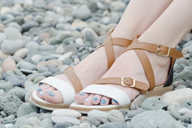 Weibliche füße in sandalen, kieselsteinen, nahaufnahme