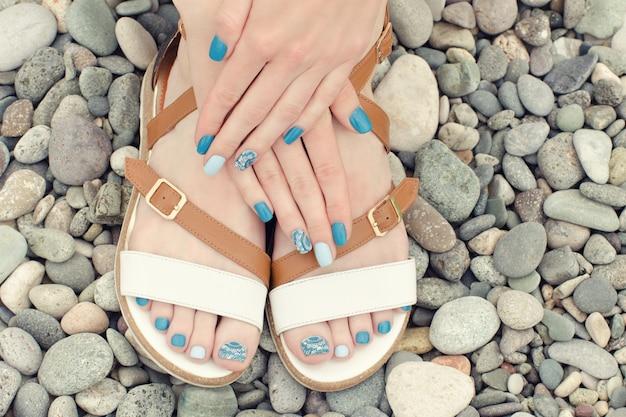 Weibliche füße in sandalen und händen mit einer blauen maniküre auf kieseln. ansicht von oben