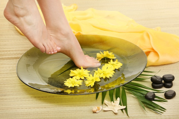 Weibliche füße in spa-schüssel mit wasser, auf bambusmatte