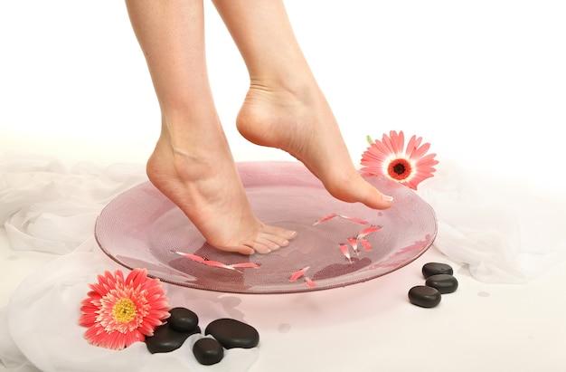 Weibliche füße in spa-schüssel mit wasser, isoliert auf weiß