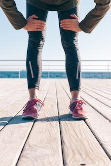 Weibliche füße in sporthosen und turnschuhen