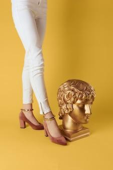 Weibliche füße kopf skulpturen goldene farbe luxus mode gelben hintergrund. hochwertiges foto