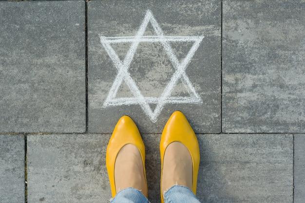 Weibliche füße mit abstraktem bild des sechszackigen sterns, geschrieben auf grauem bürgersteig
