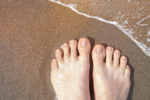 Weibliche füße mit beigem nageldesign. glitzerbeige nagellack-pediküre auf ozeanstrandsand. pediküre im sommerurlaub.