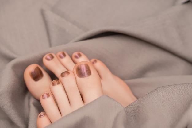Weibliche füße mit beigem nageldesign. glitzerbeige nagellackpediküre auf grauem stoffhintergrund.